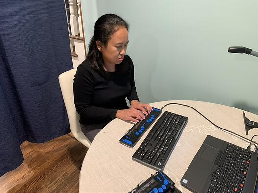 A woman works at a computer station using a screen reader.