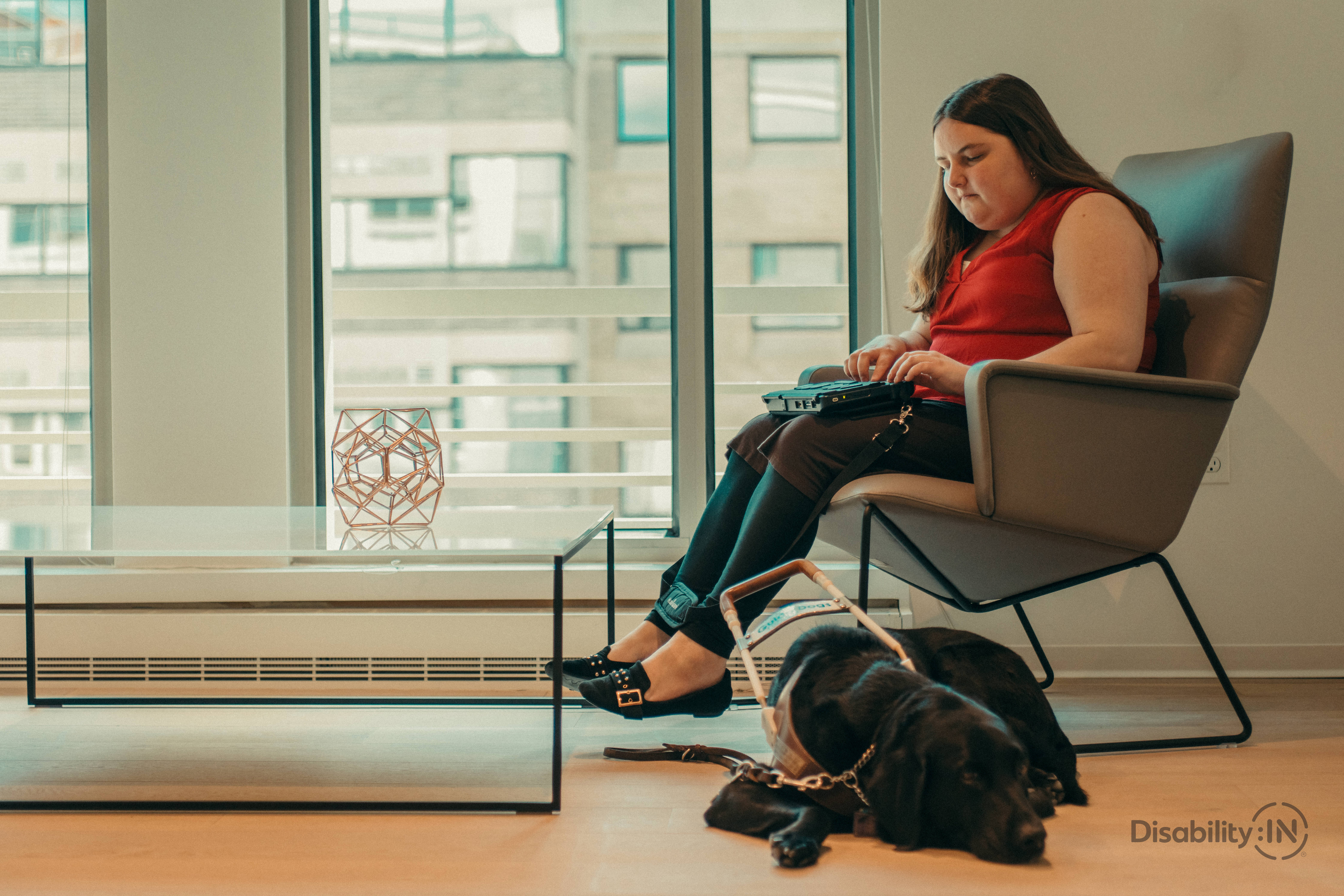 A young woman uses a screen reader with her assistance dog by her feet.